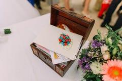 Boîte en bois pour épouser des enveloppes d'argent sur la table décorée par les fleurs colorées images stock
