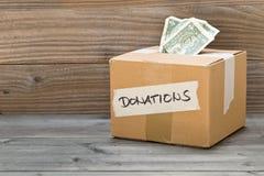 Boîte en carton de donation avec des billets de banque du dollar Photographie stock