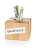 Boîte en carton de donation avec des billets de banque et des pièces de monnaie du dollar Photos libres de droits