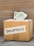 Boîte en carton de donation avec des billets de banque et des pièces de monnaie du dollar Photographie stock libre de droits