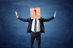 Boîte en carton de port d'homme d'affaires avec le point d'exclamation tiré sur sa tête Image libre de droits