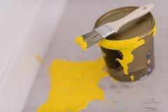 Boîte en fer blanc de peinture jaune avec la brosse sur le dessus Photo libre de droits