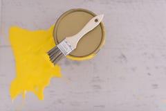 Boîte en fer blanc de peinture jaune avec la brosse sur le dessus Images stock