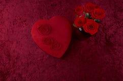 Boîte en forme de coeur à chocolat de Valentine Themed Background With et rouge Rose Bouquet sur le fond de velours écrasé par ro Photographie stock libre de droits