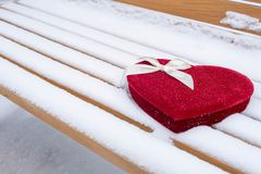 Boîte en forme de coeur à sucrerie de velours sur un banc de parc dans la neige Images stock