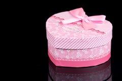 Boîte en forme de coeur rose au-dessus de fond noir avec des réflexions Image stock
