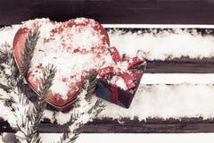 Boîte en forme de coeur rouge de bidon avec un boîte-cadeau et un fragment d'une goupille Photo stock