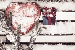 Boîte en forme de coeur rouge de bidon avec un boîte-cadeau et un fragment d'une goupille Photos libres de droits