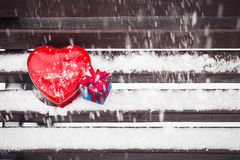 Boîte en forme de coeur rouge de bidon et un boîte-cadeau sur un banc couvert de Image stock
