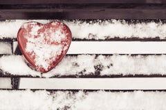 Boîte en forme de coeur rouge de bidon sur un banc Image stock