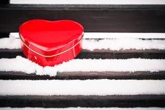 Boîte en forme de coeur rouge de bidon sur un banc couvert de neige Photo libre de droits