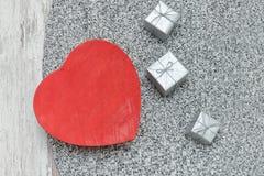 Boîte en forme de coeur rouge sur un chandail tricoté Cadres de cadeau argentés Fa photos stock