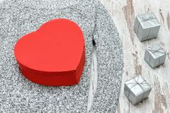 Boîte en forme de coeur rouge sur un chandail tricoté Cadres de cadeau argentés Fa photo stock