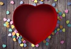 Boîte en forme de coeur rouge vide avec de mini coeurs sur le fond en bois Photographie stock libre de droits