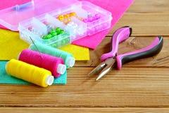Boîte en plastique avec les perles colorées, un ensemble de fil, aiguille, pinces, feuilles de feutre sur le fond en bois Image libre de droits