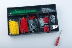 Boîte en plastique noire avec les détails de constructeur en métal intérieurs et le tournevis sur le fond blanc Photographie stock libre de droits
