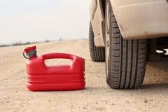 Boîte en plastique rouge d'essence sur le chemin de terre avec le véhicule Photographie stock libre de droits