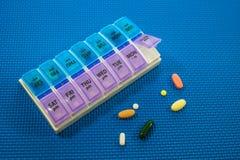 Boîte et médecine de pilule sur le fond bleu Image stock