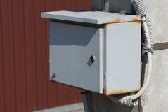 Boîte grise en métal pour l'électricité sur un poteau dehors image stock