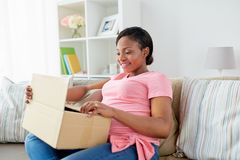 Boîte heureuse de colis d'ouverture de femme enceinte à la maison photos stock