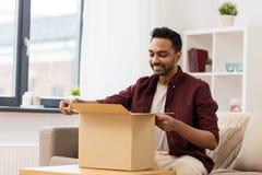 Boîte heureuse de colis d'ouverture d'homme à la maison photo libre de droits