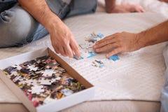 Boîte intéressante avec des puzzles se trouvant sur le lit Image stock