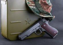 Boîte pour des balles, une arme à feu et un chapeau camouflé Photos stock