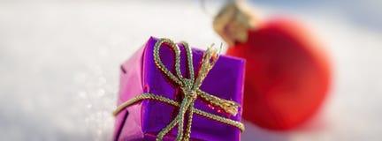 Boîte pourpre de Noël et boule rouge sur la neige Long format de bannière Image stock