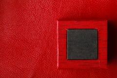 Boîte rectangulaire noire rouge d'anneau sur le fond en cuir Photographie stock libre de droits