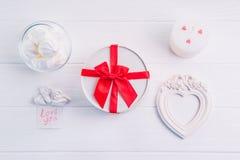 Boîte ronde blanche avec le cadre rouge de ruban, de bonbons, de bougie et de photo dans la forme du coeur Cadeaux pour le jour d Images stock