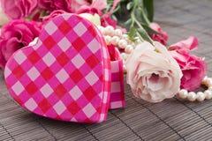 Boîte rose de coeur avec des perles et des fleurs Photographie stock