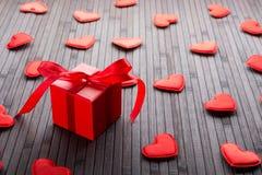 Boîte rouge avec le cadeau et les figurines des coeurs sur la table Images stock