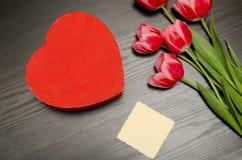 Boîte rouge dans la forme de coeur, carte propre, tulipes roses Table noire Vue supérieure, l'espace pour le texte Images stock
