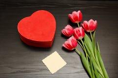 Boîte rouge dans la forme de coeur, carte propre, tulipes roses Table noire Vue supérieure, l'espace pour le texte Image libre de droits