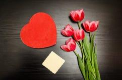 Boîte rouge dans la forme de coeur, carte propre, tulipes roses Table noire Vue supérieure, l'espace pour le texte Photo libre de droits