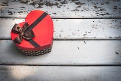 Boîte rouge dans la forme de coeur sur le fond en bois blanc Photographie stock