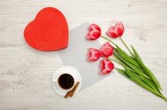 Boîte rouge dans les tulipes en forme de coeur et roses, la feuille grise et une tasse de café Table légère Images libres de droits