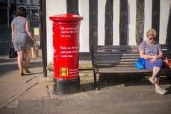 Boîte rouge de poteau avec les dames et le mur de tudor de faisceau en bois à l'arrière-plan photographie stock libre de droits