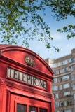Boîte rouge de téléphone des Anglais avec la construction d'art déco Photos stock