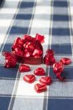 Boîte rouge en forme de coeur en métal avec des chocolats sucrés Photographie stock libre de droits
