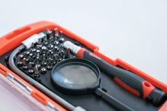 Boîte rouge pour un tournevis avec un ensemble de peu pour le travail précis avec une loupe images stock