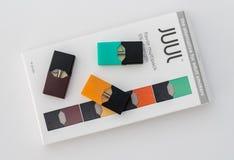 Boîte tenant le distributeur et les cosses de nicotine de JUUL photo stock