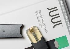 Boîte tenant le distributeur et les cosses de nicotine de JUUL images stock