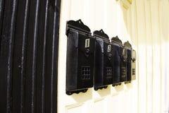 Boîtes aux lettres noires sur un mur Image stock