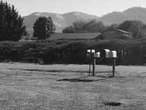 Boîtes aux lettres sur une route de campagne en noir et blanc Photographie stock libre de droits