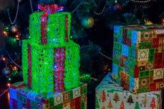 Boîtes avec des cadeaux de Noël en papier coloré décoré des guirlandes lumineuses photo libre de droits