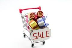 Boîtes avec des cadeaux et des barillets avec les schémas 2019/dans un chariot d'un supermarché photographie stock libre de droits