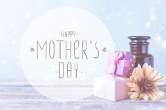 Boîtes avec des cadeaux, un bouquet des fleurs, huile cosmétique sur un fond bleu-clair avec le jour de mères heureux d'inscripti images stock