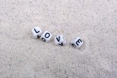 Boîtes avec l'inscription d'amour sur un sable gris Photo stock