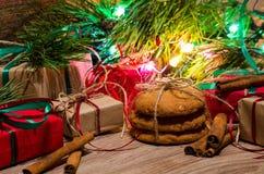 Boîtes avec les cadeaux, biscuits de pain d'épice sous le pin de Noël Photographie stock libre de droits